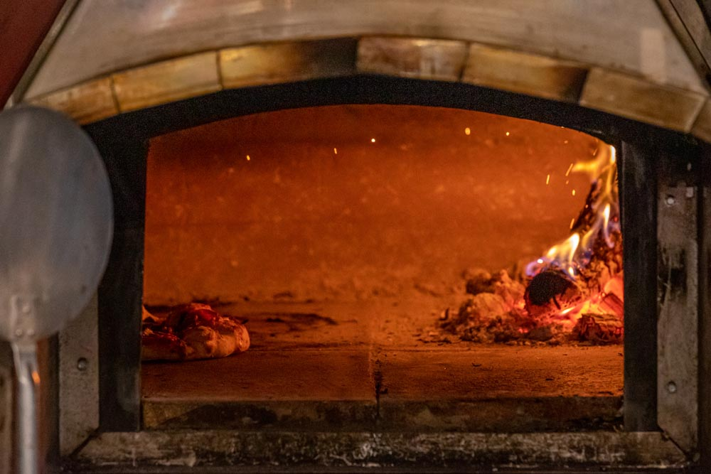 Wood burning Pizza cooking inside a woodfired oven at Embers in the Historic Hayden Granary.