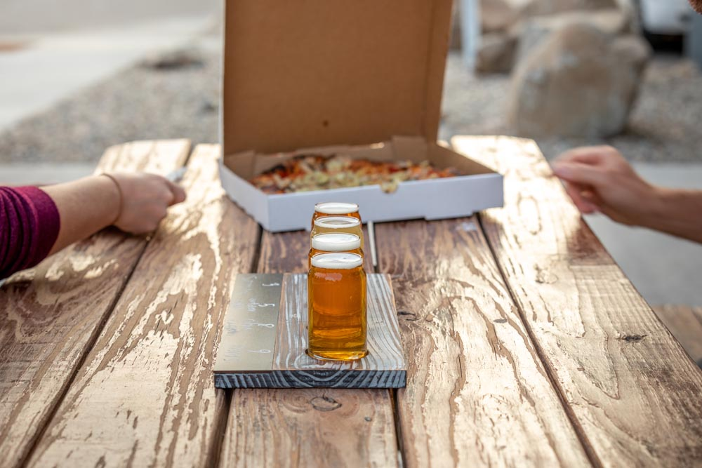 Detailed shot of guest enjoying pizza and beer at the Historic Hayden Granary.