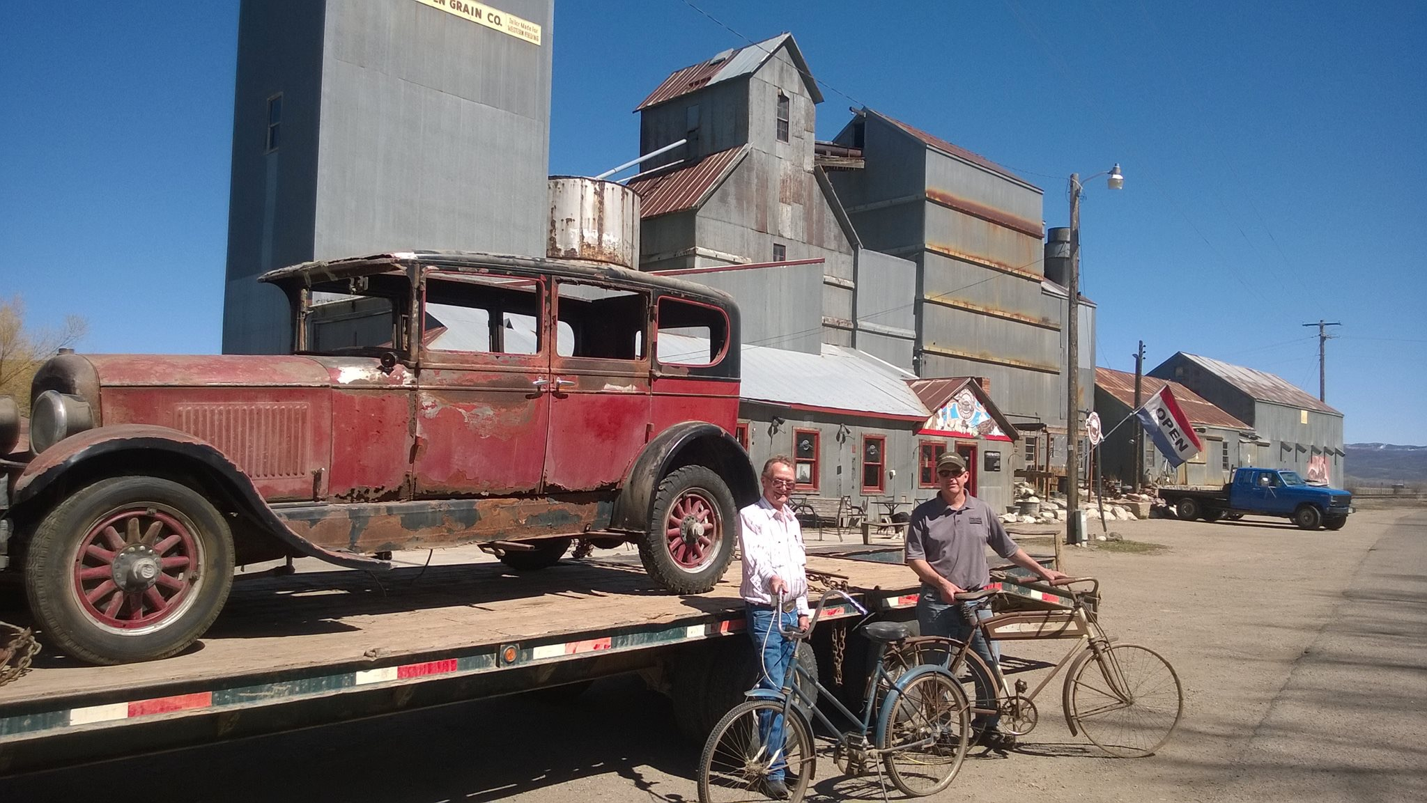 Vintage Car on trailer with two men holding vintage bikes in front of the Historic Hayden Granary.