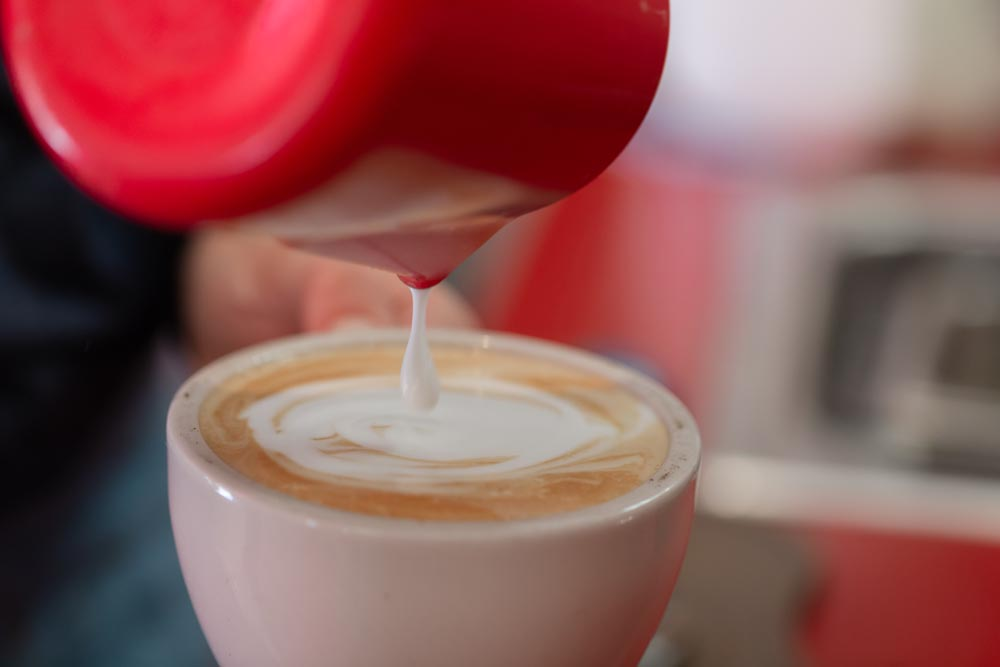 Details shot of steamed milk being poured at the Wild Goose Coffee shop.