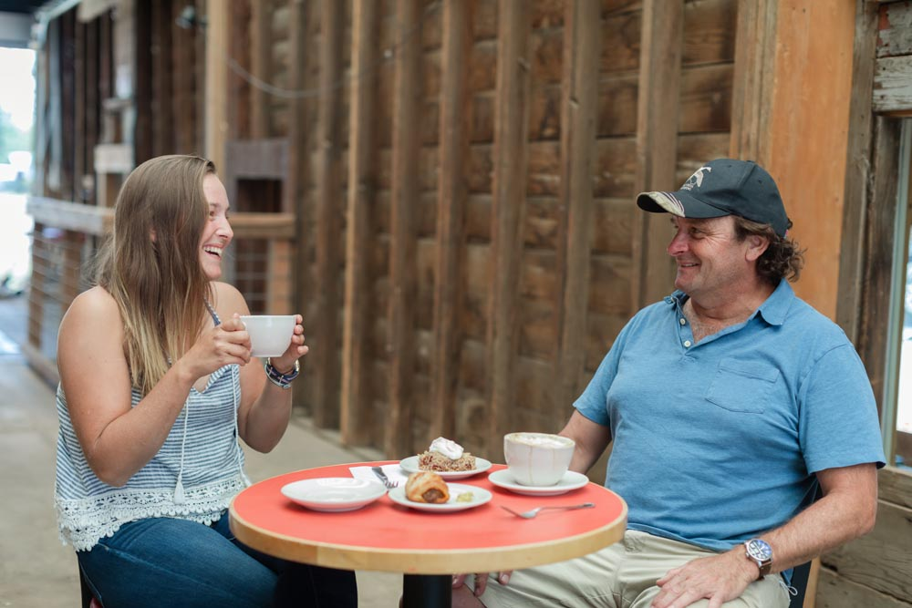 Patrons laughing together as they enjoy coffee and food from Wild Goose Granary inside the Historic Hayden Granary.