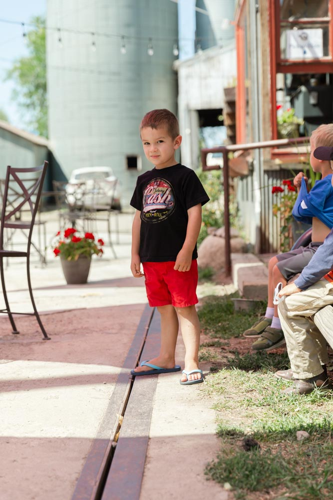 Little boy standing outside of the Wild Goose Coffee shop at the Historic Hayden Granary.