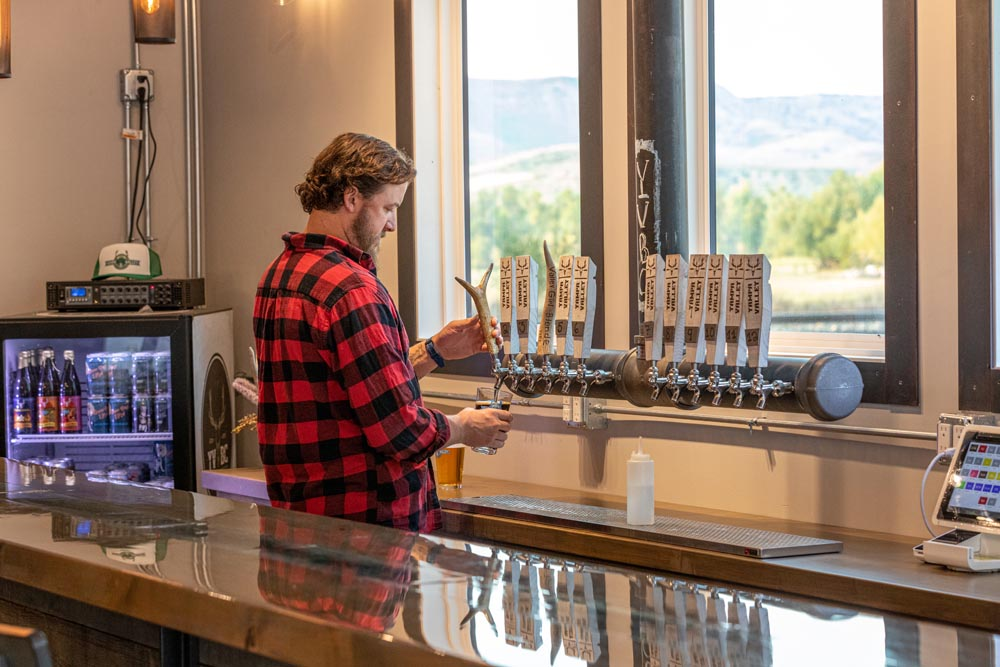 Yampa Valley Brewing Brew master pouring a beer on tap.